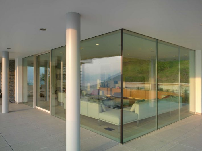 Vista esterna della parete vetrata ad angolo con fissi a tutt'altezza della zona living