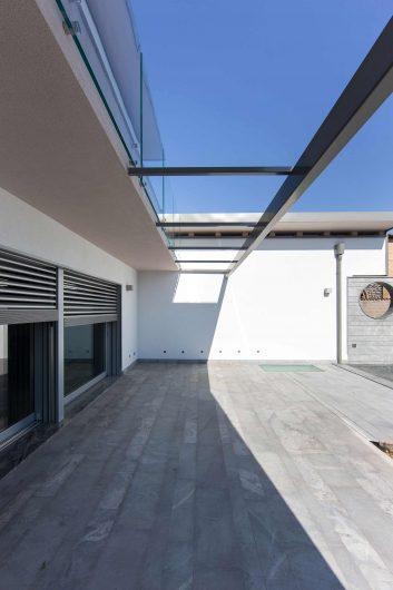 Vista del patio esterno con copertura vetrata e frangisole in alluminio motorizzati