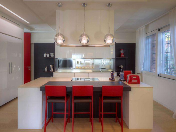 Vista dell'area cucina con alzante scorrevole laccato bianco
