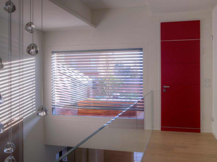 Vista interna dell'ingresso secondario con portoncino e serramento fisso