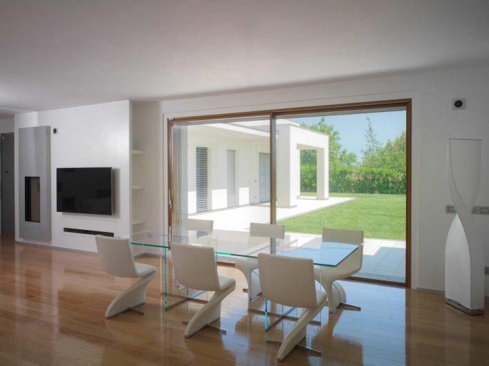 Alzante scorrevole in legno a due ante con finitura naturale, vista interna della sala da pranzo