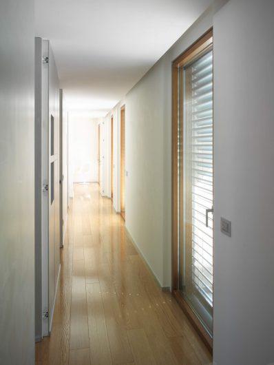 Vista del disimpegno con porta finestre in legno ad anta singola
