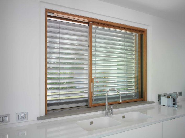 Finestra scorrevole della cucina, in legno con finitura naturale e frangisole in alluminio abbassato