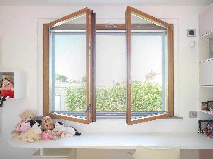 Finestra in legno a due ante aperte con finitura naturale