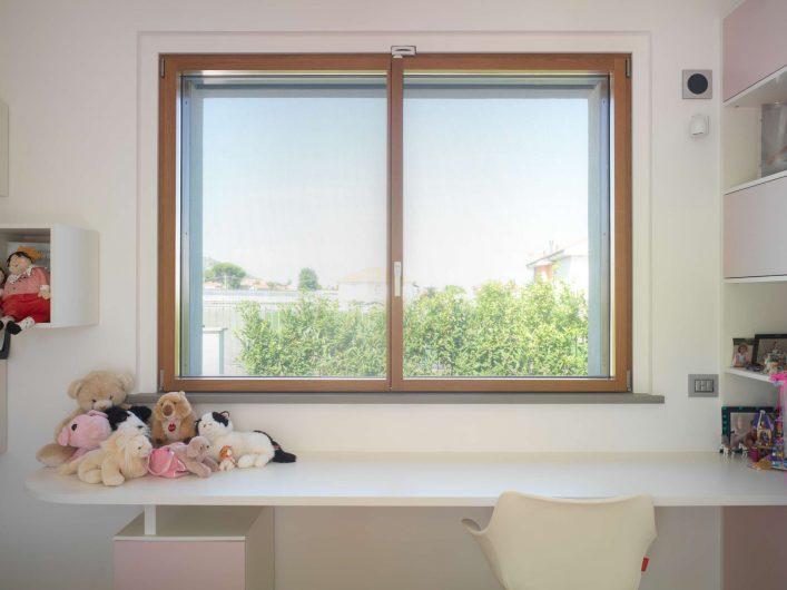 Finestra in legno a due ante chiuse con finitura naturale