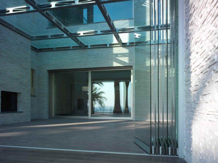 Dettaglio del serramento a bifold in vetro e portico esterno con alzante scorrevole Invitrum