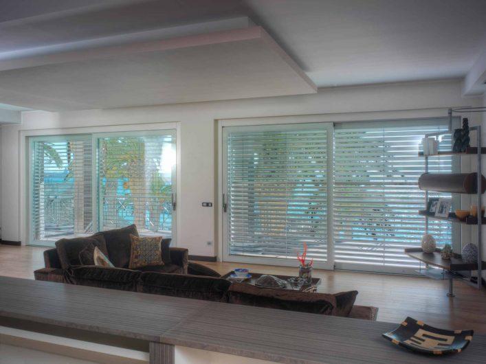 Zona living con alzanti scorrevoli a due ante e frangisole in alluminio abbassati