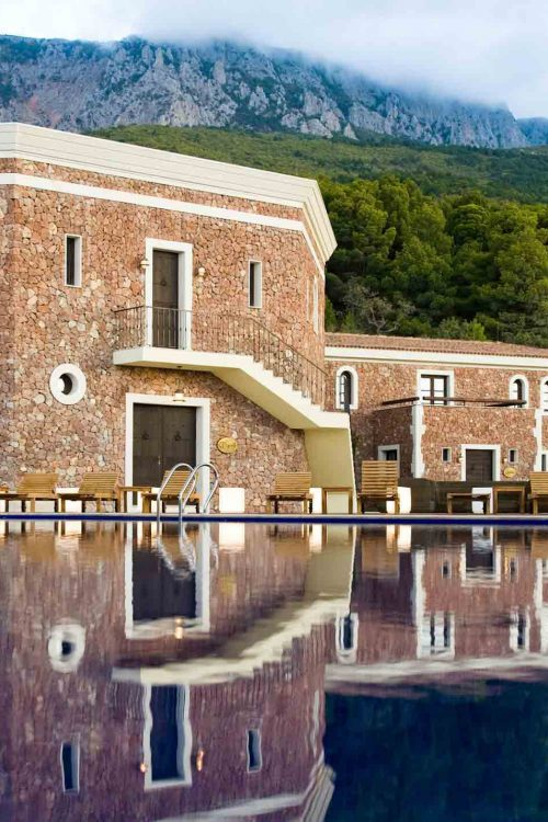 Vista del prospetto principale dell'hotel affacciato sulla piscina con finestre e portoncini in legno