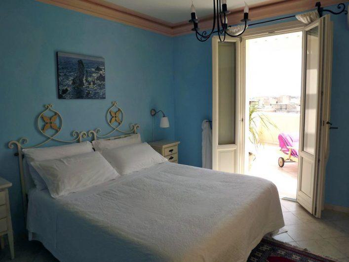 Vista di una camera matrimoniale all'Hotel Egadi con porta finestra laccata in stile classico