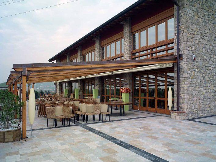 Vista generale della terrazza comune dell'Hotel Fontana Santa con sistema di serramenti in legno color noce con grandi aree finestrate
