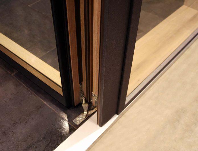 Dettaglio della cerniera inferiore della portiera rivestita in alluminio