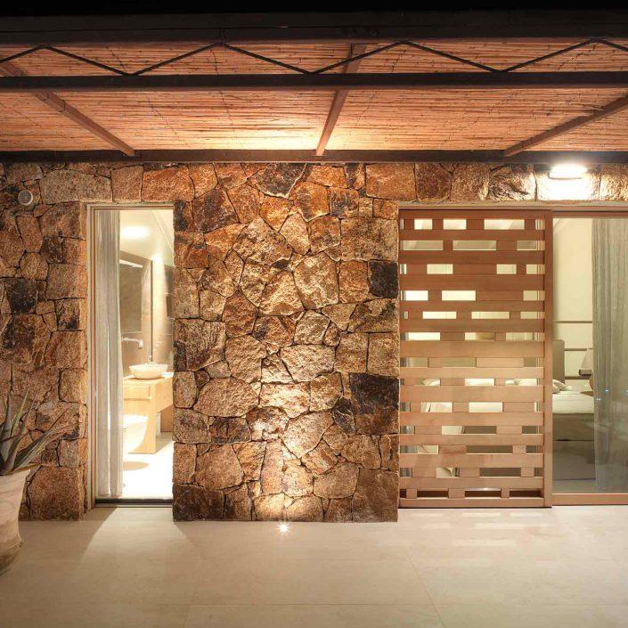 Villa Costa Smeralda, particolare della facciata in pietra con porta finestra, alzante e frangisole scorrevole