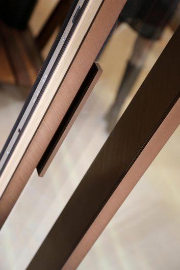 Dettaglio del maniglione di un alzante rivestito in alluminio color bronzo spazzolato