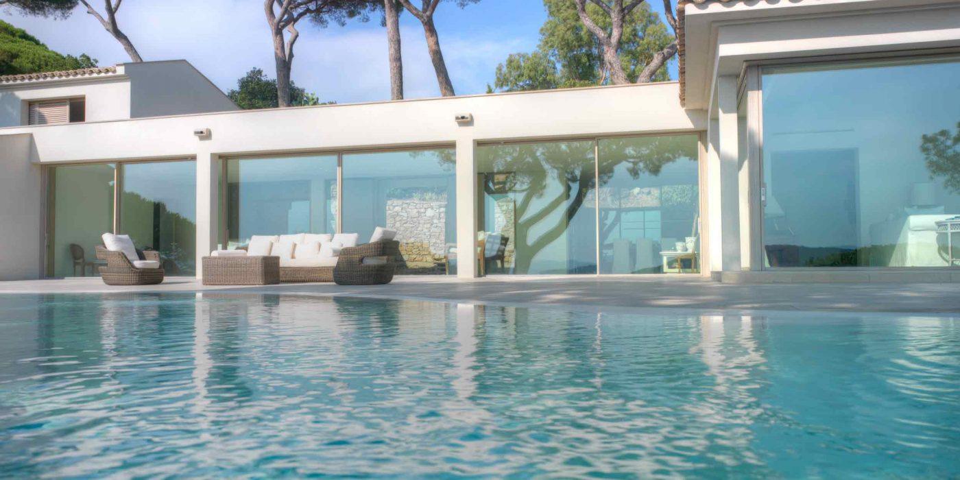 Vista di un prospetto su piscina con parete vetrata ad alzanti scorrevoli