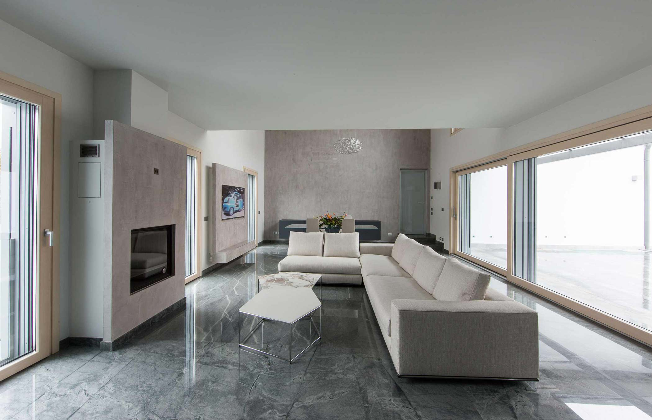 Vista di un open space con porta finestra e alzante scorrevole in legno con rivestimento in alluminio