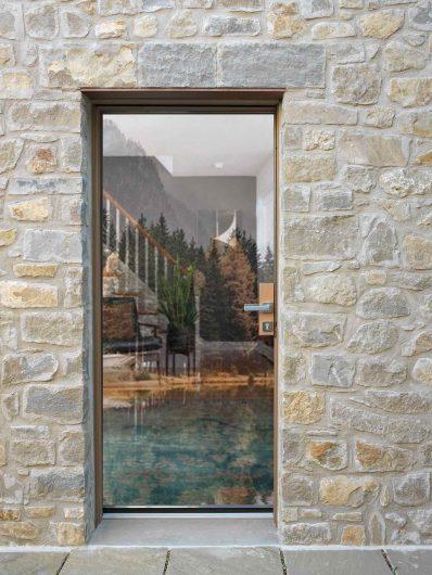 Vista esterna di una porta d'ingresso con maniglia passante e vetro strutturale effetto vitrum