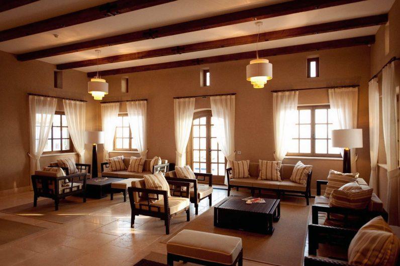 Vista di un'area sedute con finestre e porte finestre a due ante in legno effetto naturale