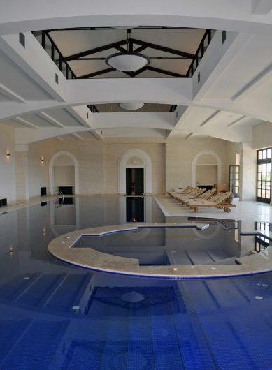 Vista della piscina coperta con porte finestre con fuseruoli sullo sfondo