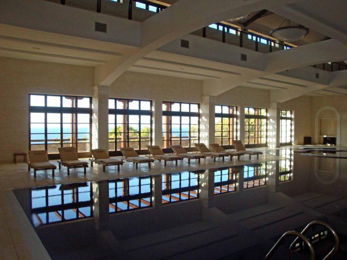 Vista della parete vetrata della piscina con sistema di aperture a porta finestra e fissi sopraluce