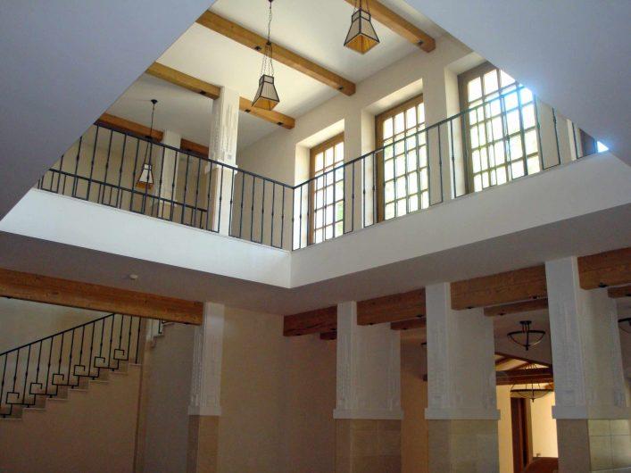 Vista del portico interno dell'hotel con porte finestre in legno al piano superiore