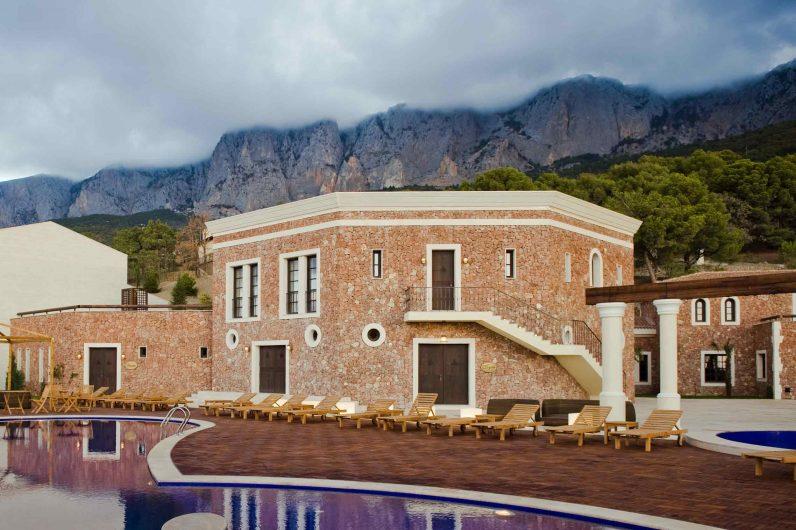 Vista del patio esterno sulla piscina e corpo di fabbrica dell'hotel con serramenti in legno custom