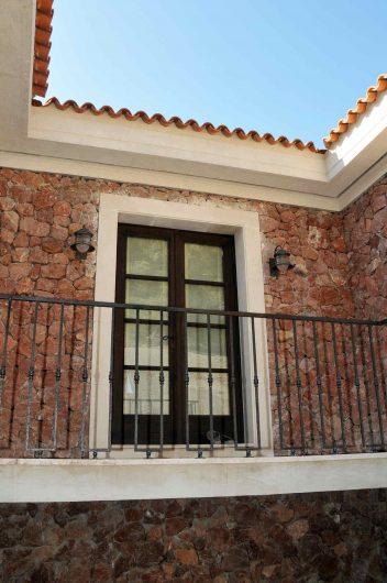 Vista esterna di una porta finestra a due ante con fuseruoli in legno