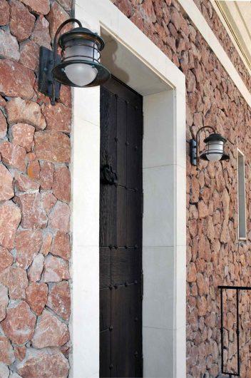 Vista di dettaglio di un portoncino in legno cieco con dettagli in bronzo