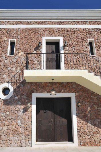 Vista della facciata del residence con portoncino cieco a due ante in primo piano