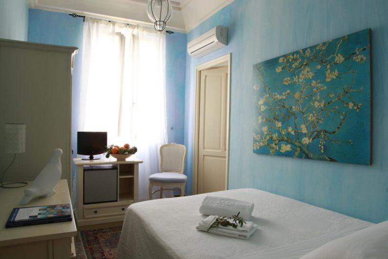 Interno di una camera da letto dell'Hotel Egadi con finestra a due ante in legno