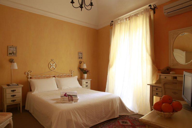 Vista d'interno di una camera da letto con porta finestra nascosta dai tendaggi