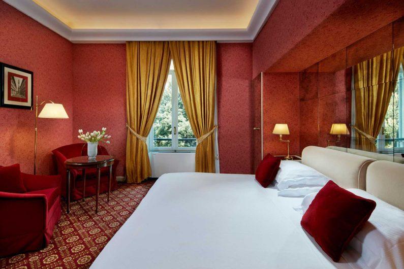 Vista di una camera da letto con finestra a due ante in legno laccato bianco sullo sfondo