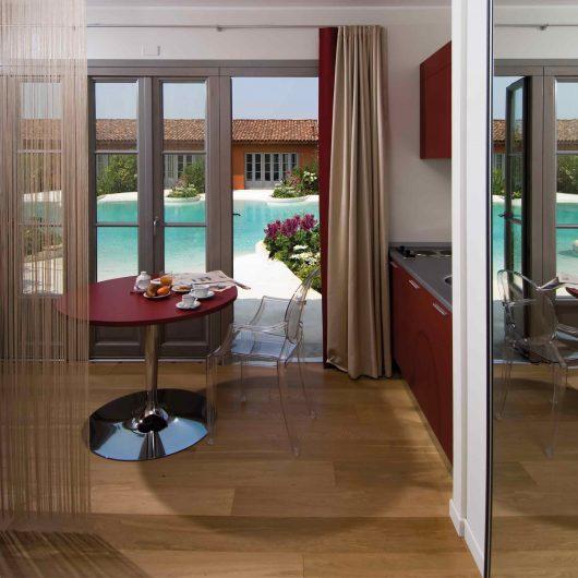 Vista dello spazio cucina con porta finestra in legno laccato sullo sfondo