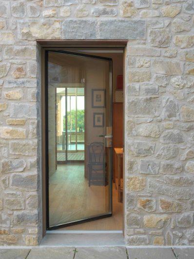 Vista frontale della portiera vetrata con maniglia passante satinata