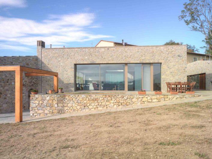 Vista frontale dela parete vetrata della zona living con alzante scorrevole chiuso, vetrate fisse e porta finestra Skyline