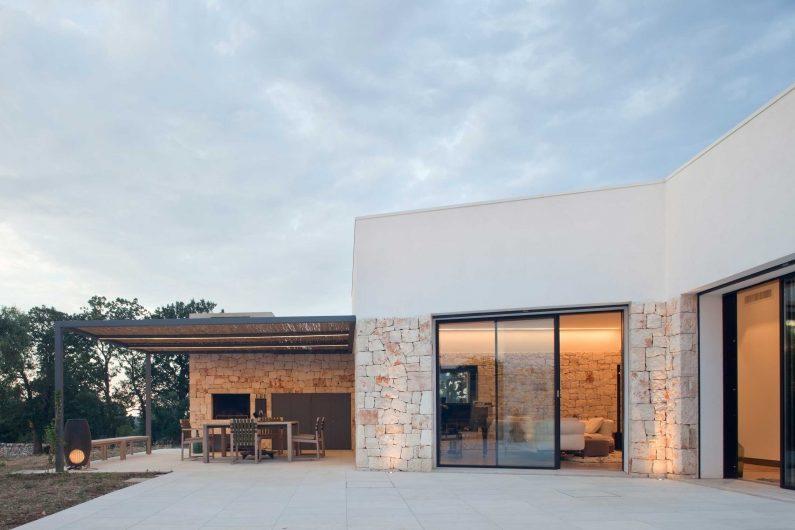 Vista del patio esterno con alzanti scorrevoli a due ante asimmetriche in abete mordenzato scuro