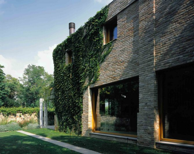 Vista della facciata laterla ein mattoni di recupero con finestre e vetrate fisse in legno di rovere