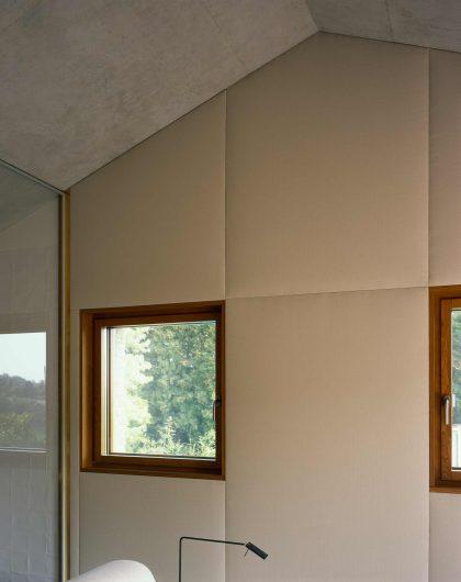 Vista della parete interna di una camera rivestita con boiserie, con finestra ad anta singola in rovere