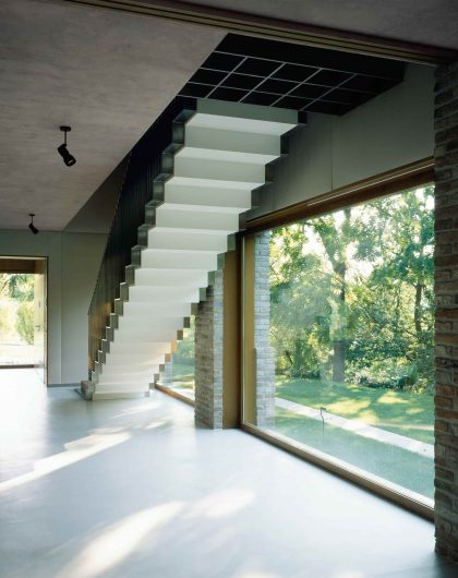 Vista interna della scala con vetrate fisse in rovere effetto naturale