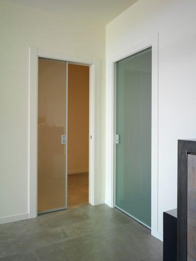 Vista di due porte interne scorrevoli in alluminio e vetro