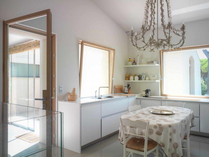 Vista della cucina con porta d'ingresso vetrata e due finestre aperte a vasistas