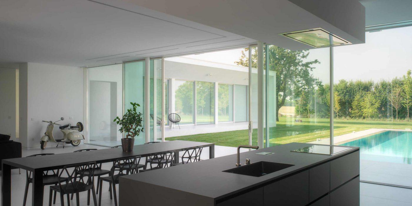 Vista della zona cucina con alzante scorrevole a quattro ante sullo sfondo