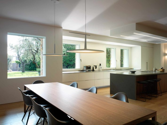 Vista dell'open space zona cucina e pranzo con fisso incassato e finestre a filo muro laccate bianche