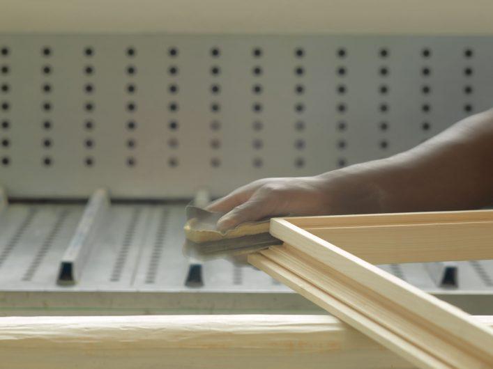 Vista di un falegname durante la carteggiatura di un profilo
