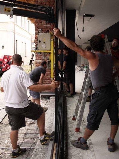 Vista di un gruppo di tecnici impegnati nella posa in opera di una vetrata fissa