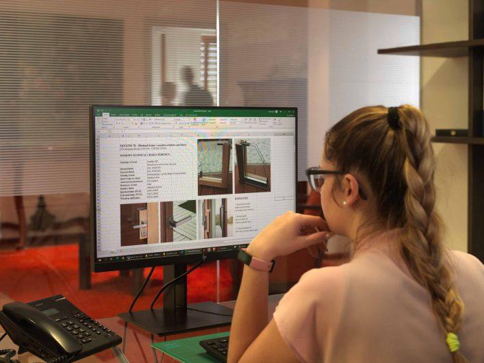 Vista dell'impiegata durante la redazione di un preventivo al computer