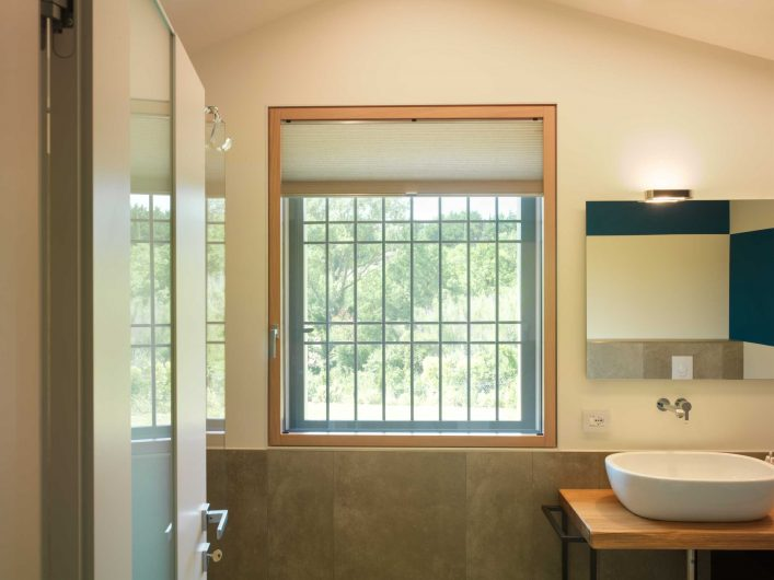 View of the single sash bathroom window with mosquito net and iron grating