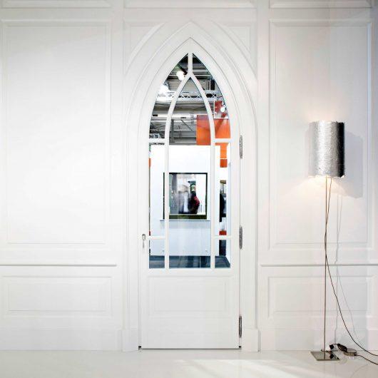 Vista frontale di una porta ad arco acuto con parete in boiserie bianca