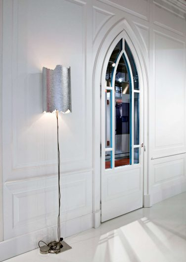 Vista di scorcio di una parete con boiserie bianca classica e porta ad arco