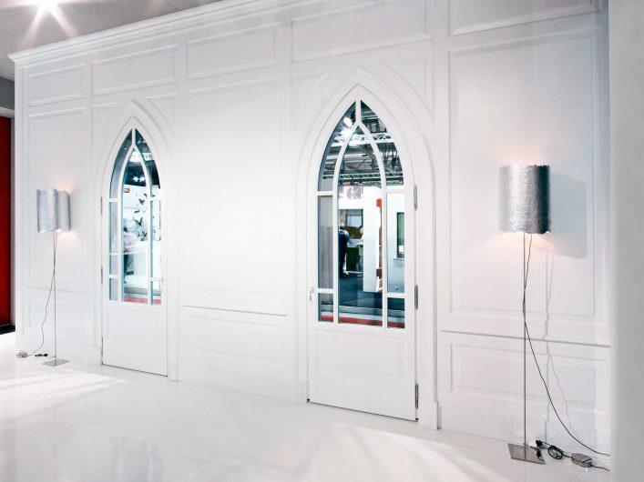 Vista di una parete rivestita da una boiserie in legno bianca con cornici classiche