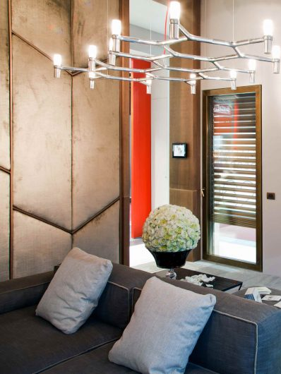 Vista di un interno con parete rivestita da boiserie in velluto e dettagli in legno